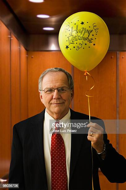 Senior man holding a balloon in an elevator