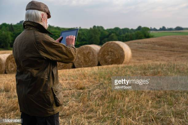 senior man holding a digital tablet in a field - johnfscott stock pictures, royalty-free photos & images