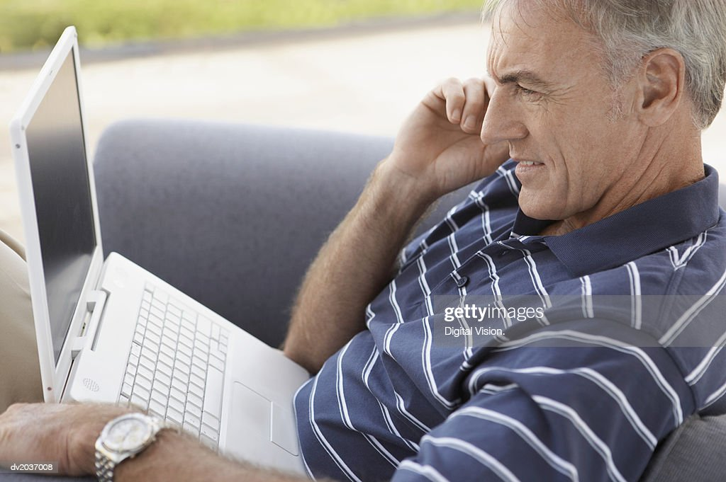 Senior Man Holding a Mobile Phone and Using a Laptop : Stock Photo