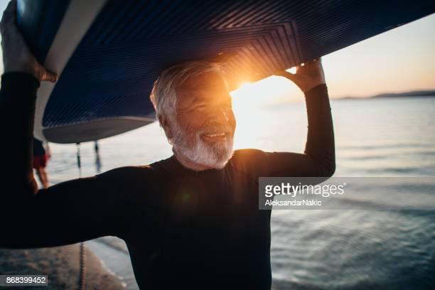 Senior man holding a paddle board