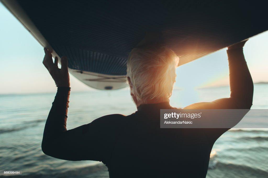 Senior man holding a paddle board : Stock Photo
