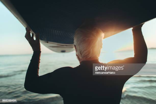 senior man holding a paddle board - baby boomer stock pictures, royalty-free photos & images