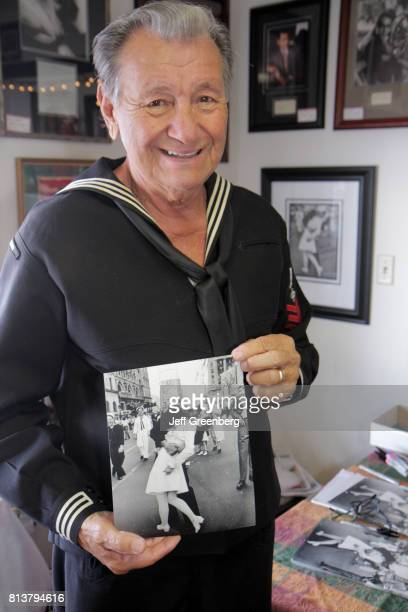 A senior man holding a Sailor kissing girl in Times Square photograph at the Annual Craft Fair in Mount Dora