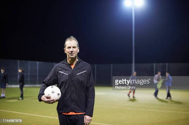 senior man holding a soccer ball - floodlit stock pictures, royalty-free photos & images
