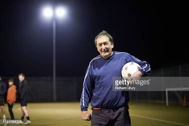 senior man holding a soccer ball - sport venue stock pictures, royalty-free photos & images