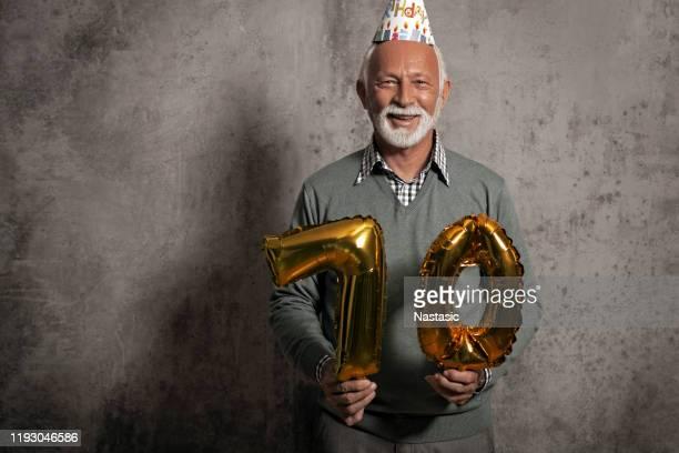 senior man holding ballonnen voor 70e verjaardag - 70 79 jaar stockfoto's en -beelden