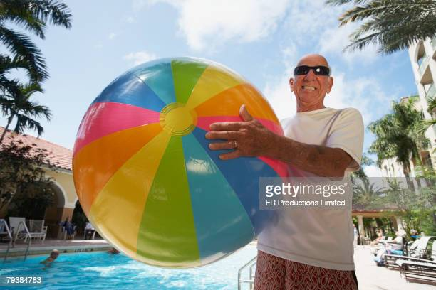 senior man holding beach ball - man with big balls stock photos and pictures