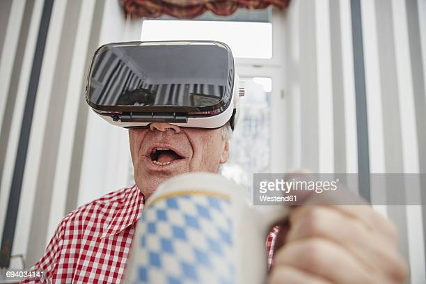 Senior man holding beer mug wearing VR glasses