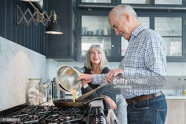 Senior man holding bowl making dinner, his wife is watching