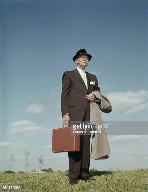 senior man holding briefcase and standing in park - einzelner senior stock-fotos und bilder