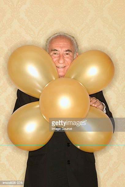 Senior man holding bunch of balloons