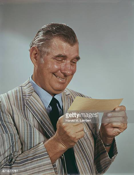 senior man holding check and smiling  - {{ contactusnotification.cta }} stock pictures, royalty-free photos & images