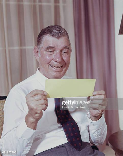 senior man holding check and smiling  - {{relatedsearchurl(carousel.phrase)}} imagens e fotografias de stock