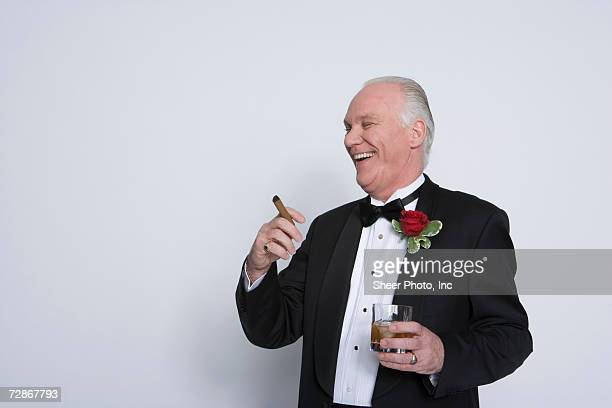 Senior man holding cigar and glass of whisky, smiling