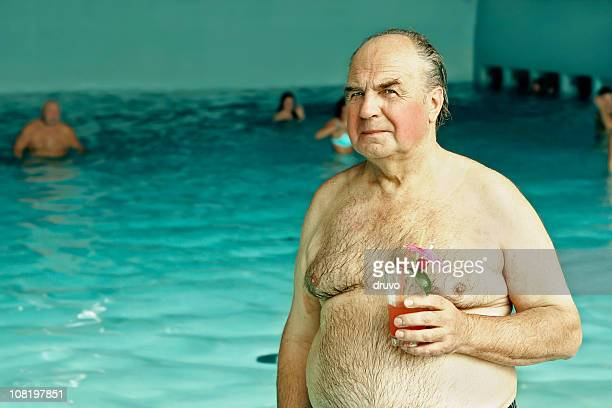 senior man holding cocktail drink near swimming pool - hairy old man stock pictures, royalty-free photos & images