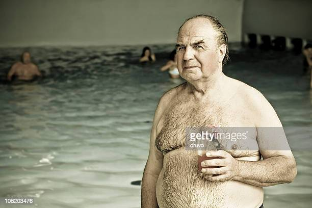 Senior Man Holding Cocktail Drink Near Swimming Pool