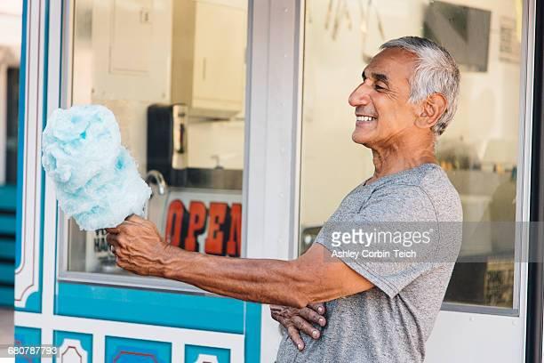 Senior man holding cotton candy, Long Beach, California, USA