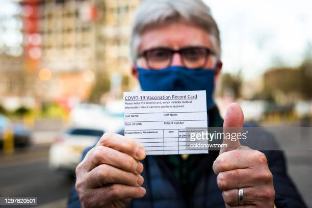 senior man holding covid-19 vaccination record card - certificate stock pictures, royalty-free photos & images