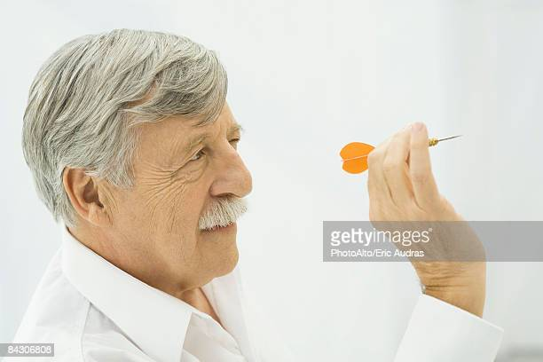 Senior man holding dart, aiming