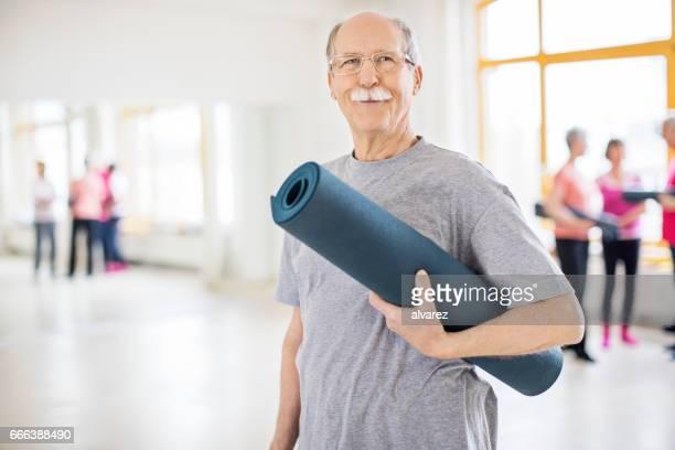 Senior woman Gymnastikmatte in Yoga-Kurs halten