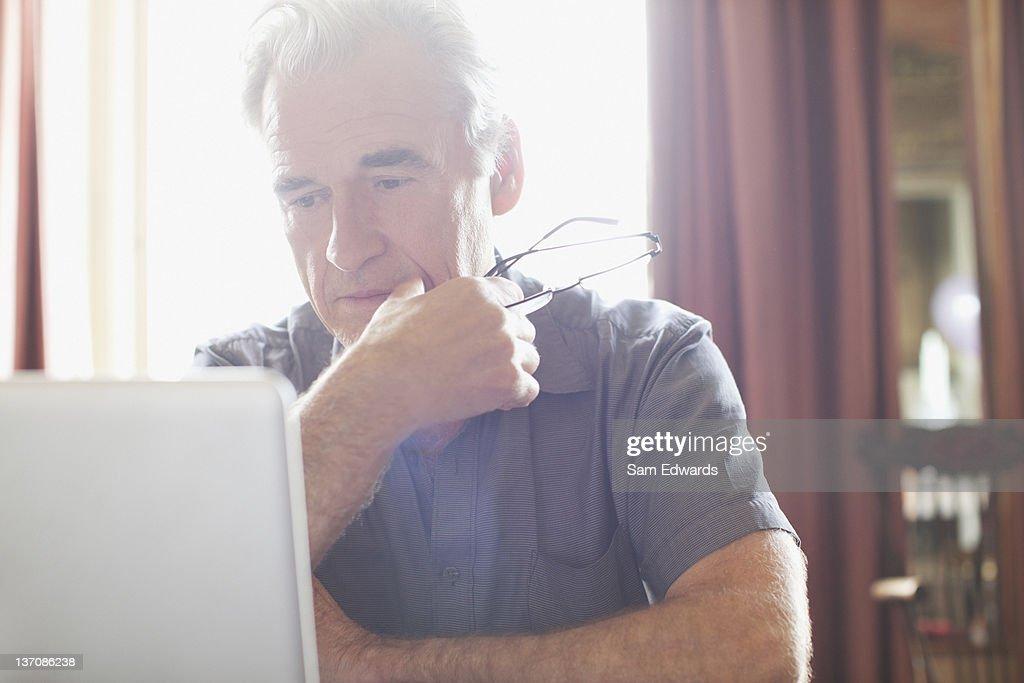 Senior man holding eyeglasses and using laptop : Stock Photo