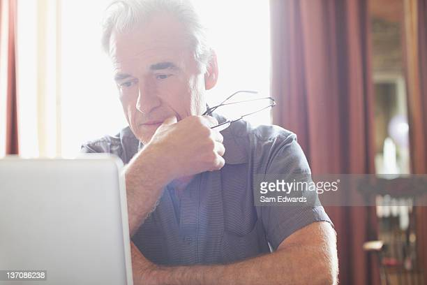 Senior man holding eyeglasses and using laptop