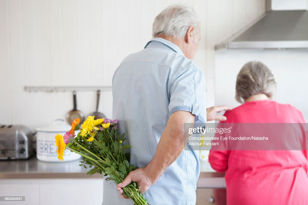 Senior man holding flowers behind back for wife : Stock Photo