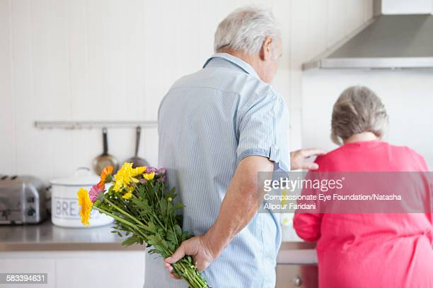 Senior man holding flowers behind back for wife