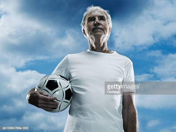 Senior man holding football in front of clouds