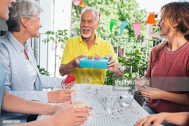 senior man holding gift at family party - streamer stock photos and pictures