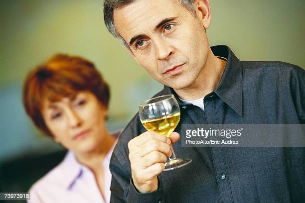 Senior man holding glass of wine, senior woman looking at him in background