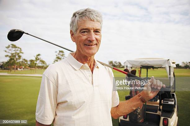 Senior man holding golf club, golf cart in background, portrait