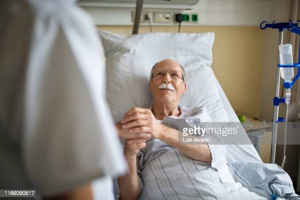senior man holding hand of female nurse in hospital room - ziekenhuis stockfoto's en -beelden