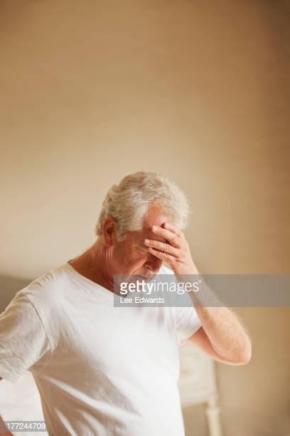 Senior man holding head in pain