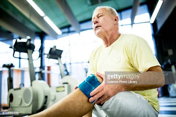senior man holding ice pack on knee - human knee stock pictures, royalty-free photos & images