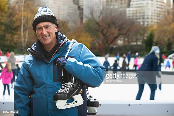 Senior man holding ice skates