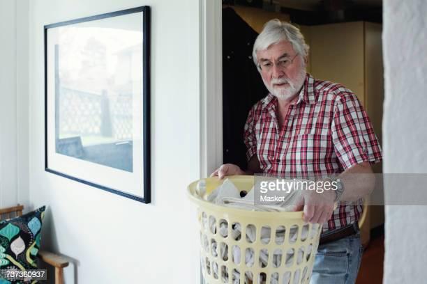 Senior man holding laundry basket while walking through doorway at home