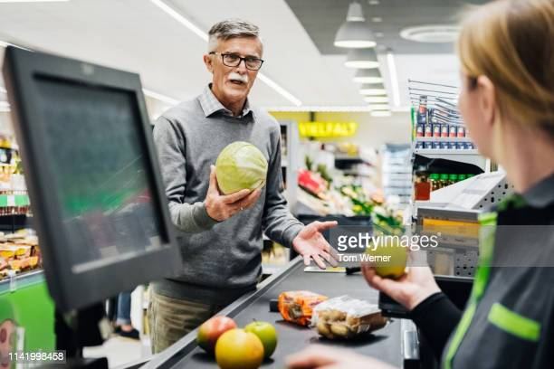senior man holding melon and talking to cashier - till stock pictures, royalty-free photos & images