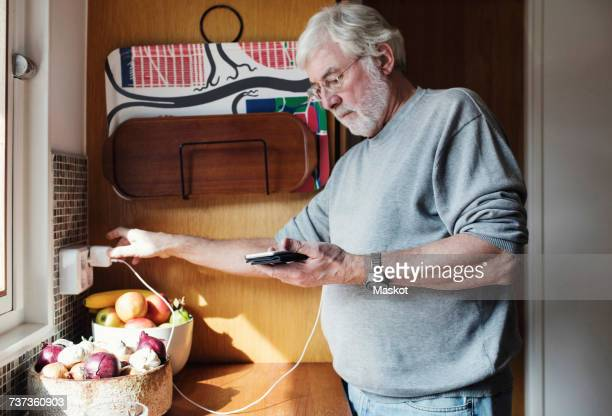 Senior man holding mobile phone while plugging charger to electrical outlet at domestic kitchen