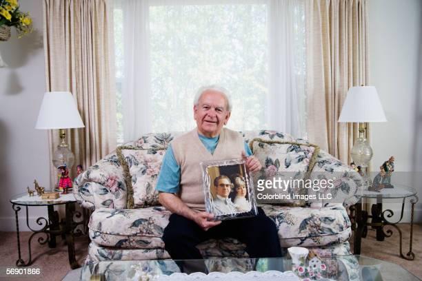 senior man holding photograph - alleen seniore mannen stockfoto's en -beelden