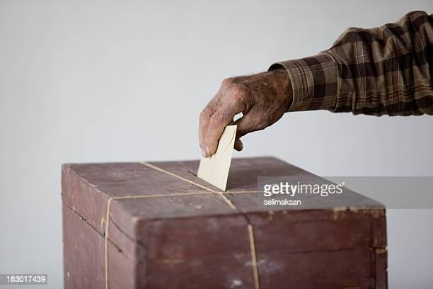 senior man holding poll envelope on locked ballot box - voting ballot stock pictures, royalty-free photos & images