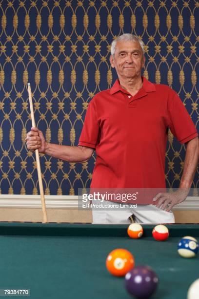 Senior man holding pool cue