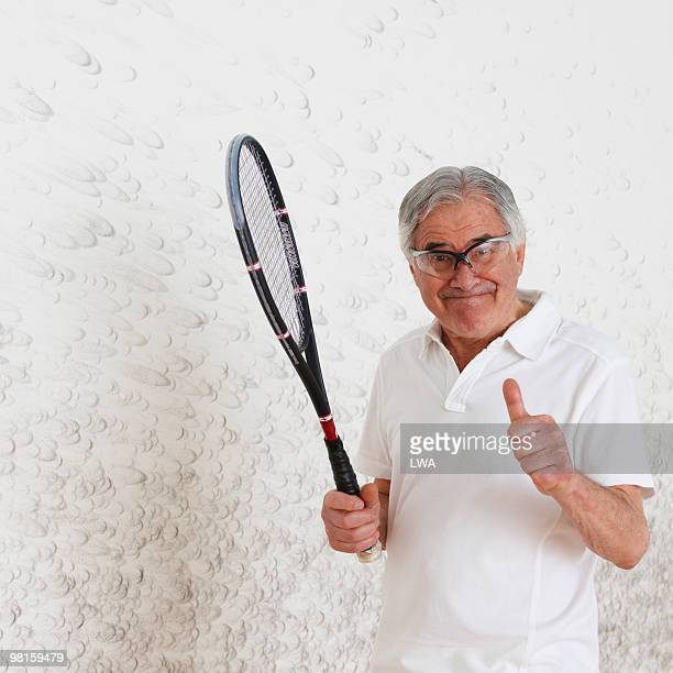Senior Man Holding Racquet, By Squash Court Wall