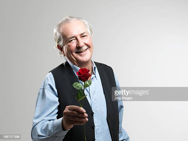 Senior man holding red rose