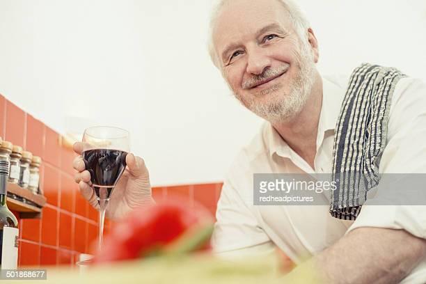 Senior man holding red wine, portrait
