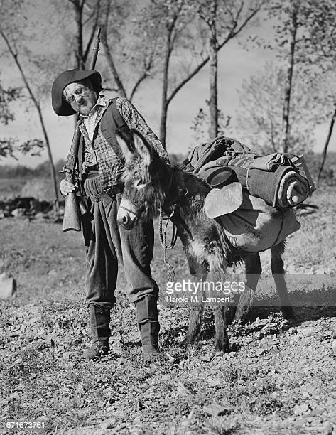 senior man holding rifle and standing besides donkey - {{ collectponotification.cta }} fotografías e imágenes de stock