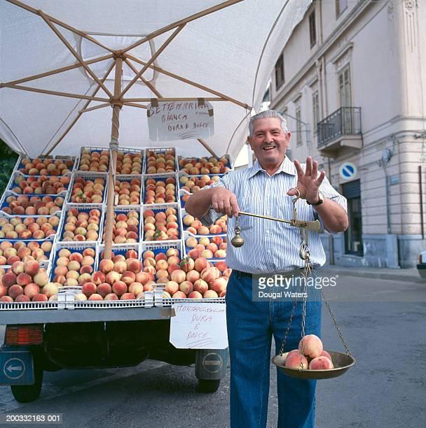 Senior man holding scales containing peaches, smiling, portrait