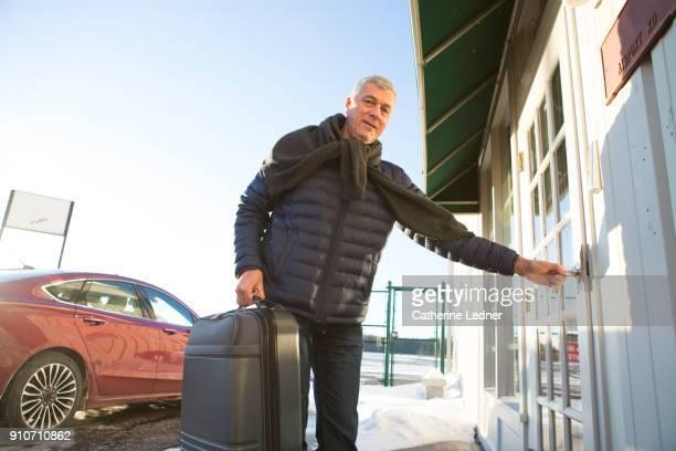 Senior man holding suitcase opening door in winter
