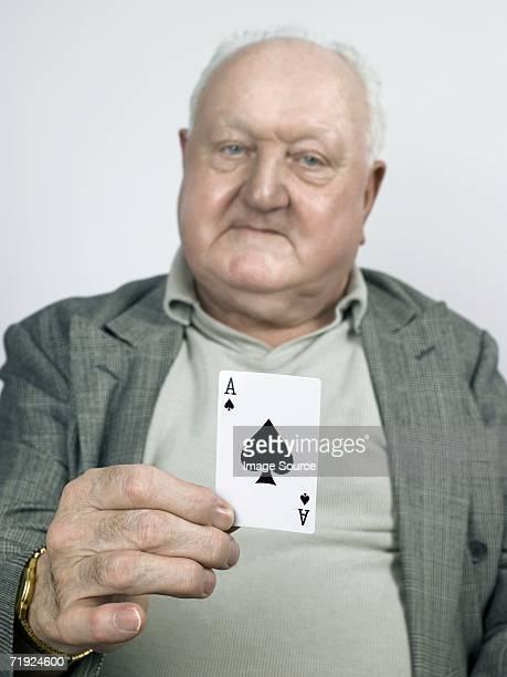 Senior man holding the ace of spades