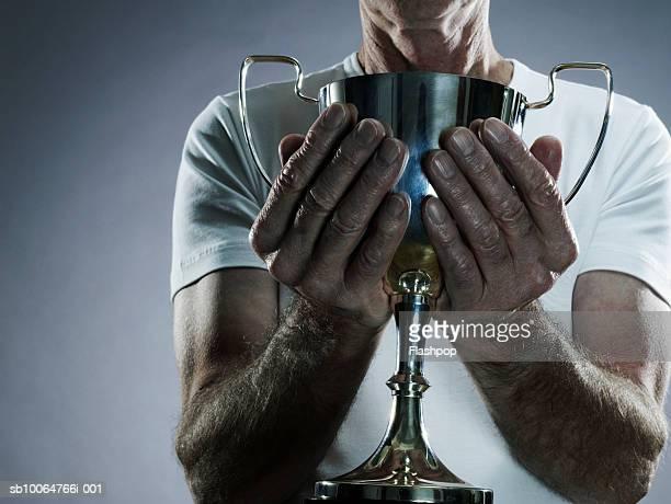 Senior man holding trophy, mid section, studio shot